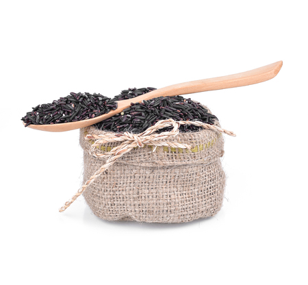 bag of black rice and a wooden spoon on a white background keeping paths