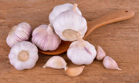 garlic in a wooden spoon on a wooden floor