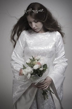 black princess: Girl in medieval white dress with a bunch of flowers