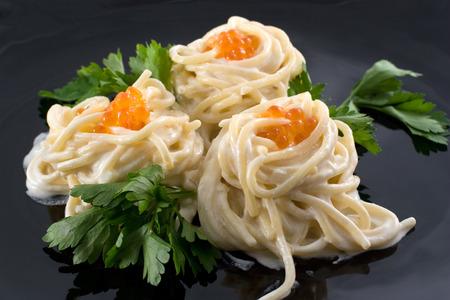 potherbs: Spaghetti con caviar rojo y verde en un plato negro