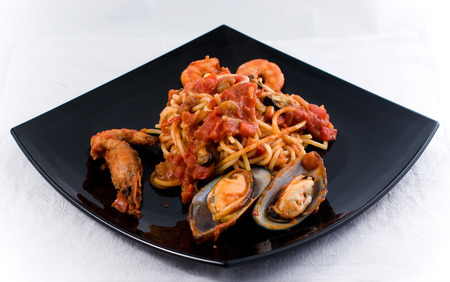 seafruit: Spaghetti Marinara with mussel om a black plate