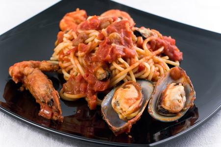 seafruit: Spaghetti Marinara with mussel om a black plate