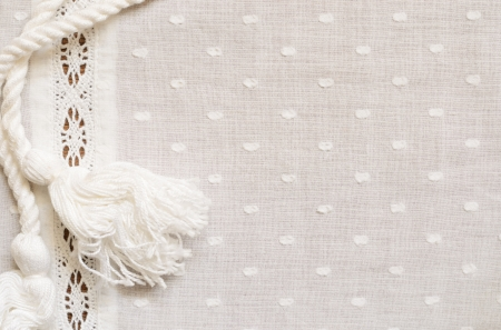 Background of spotted fabric with a strip of lace and a rope photo