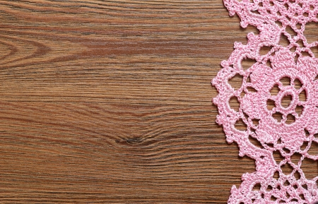 Wooden surface with the crochet lace on the edge photo