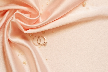 Drapery of delicate pink satin in the corner with pearls and wedding rings photo
