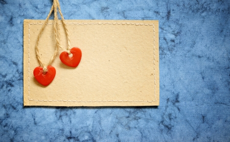Two red plastic hearts and carton card on a blue background Stock Photo - 18958487