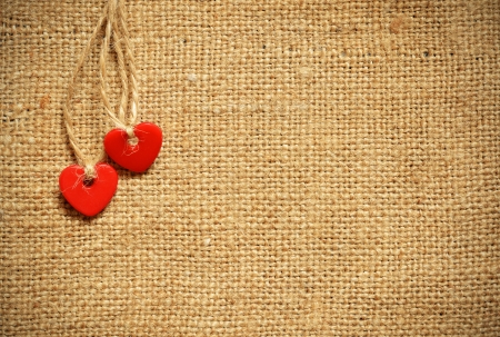 Two red plastic hearts on canvas background photo