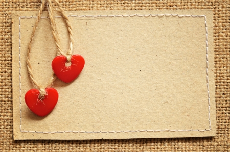 Two red plastic hearts and carton card on a canvas background