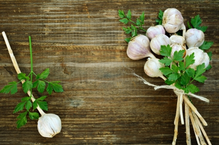 Bunch of garlic and parsley on old wooden background photo