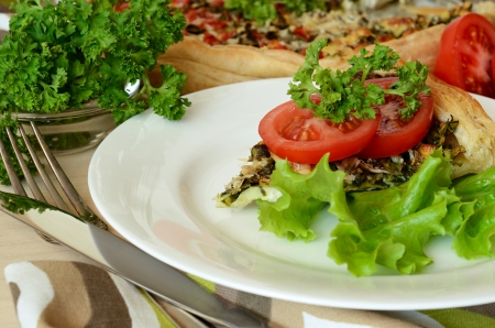 Pie with spinach and cheese served on plate with salad and tomatoes photo