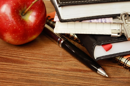 Notebooks, pen and apple on wooden table photo
