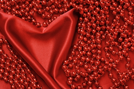 Red satin draped in the form of heart and beads photo
