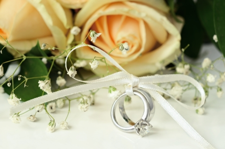 Engagement and wedding rings with bouquet of flowers