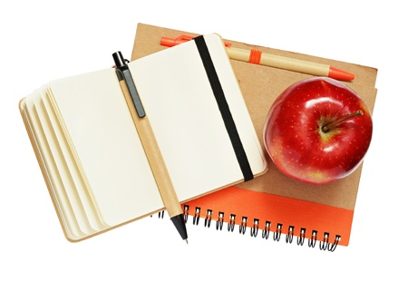 Notebooks, pens and apple isolated on white photo