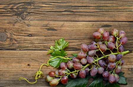 wood barrel: Bunch of grapes on old weathered wooden table