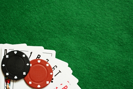 Poker chips and cards on green cloth photo