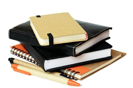 Stack of notebooks and pens Фото со стока