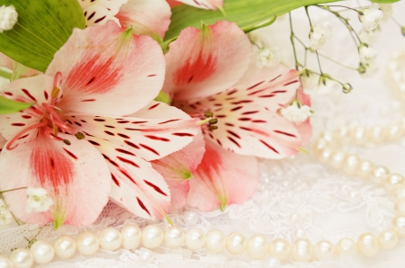 Bouquet of pink flowers and pearls on white embroidered lace