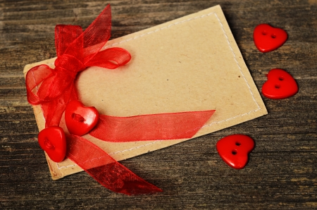 Two hearts tied with red ribbon on card photo