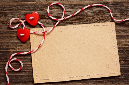 Two hearts and a card on wooden background photo
