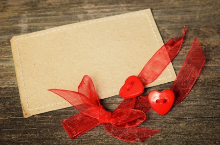 Two hearts tied with red ribbon on celebration card photo