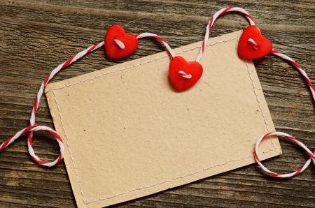Three hearts and a card on wooden background photo