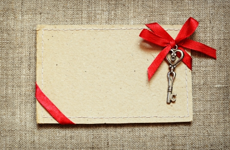 Greeting card with red ribbon and a key on canvas background photo