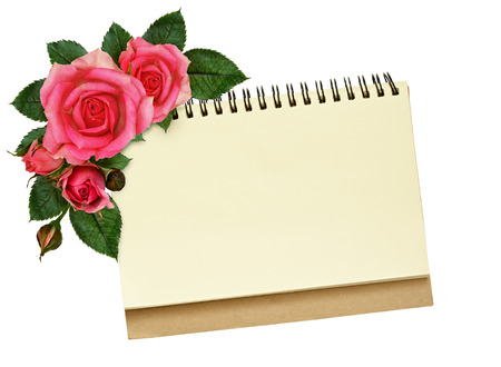 Notebook and rose flowers isolated on white photo
