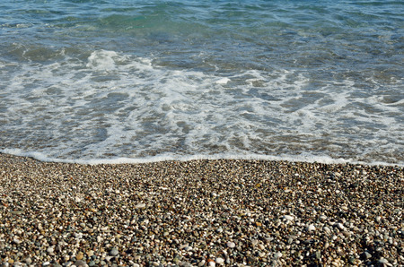 Summer background with beach pebbles and sea wave photo