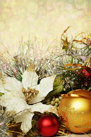 Christmas balls with tinsel and artificial poinsettia on a holiday background photo