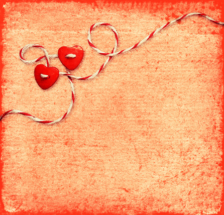 Two hearts tied with rope on old red background photo