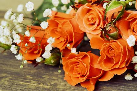 rosas naranjas: Rosas anaranjadas en fondo de madera vieja