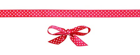 Red spotted bow and ribbon isolated on white background