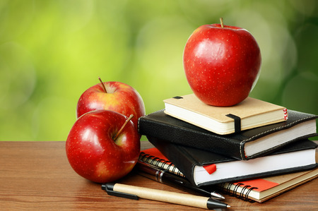 teaching material: Notebooks, pens and apples on a table with green bokeh background Stock Photo