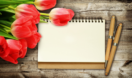 red tulip: Red tulip flowers, note and pencils on dark wooden background Stock Photo