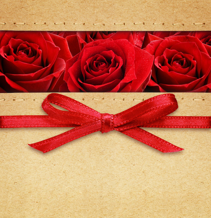 silk bow: Rose flowers and red silk bow on carton background
