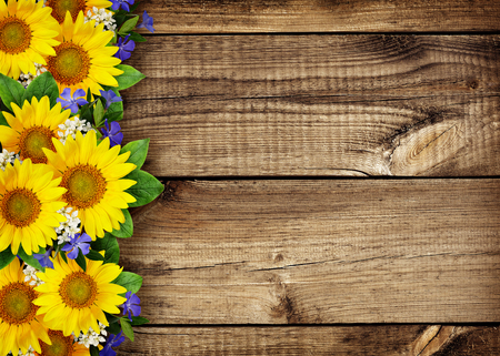 Sunflowers and wild flowers border on wooden background