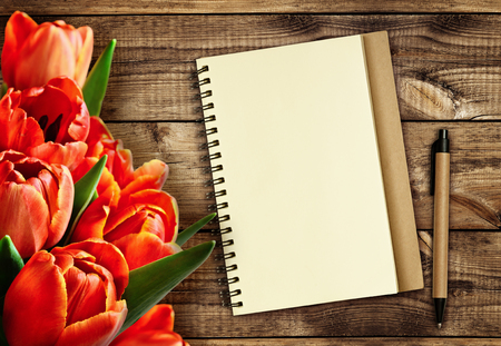 memoirs: Red tulip flowers with notebook and pen on wooden background Stock Photo