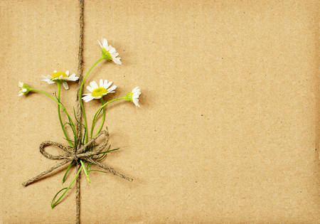 rough background: Brown cardboard package tied with daisy flowers bouquet and rope. Summer present.