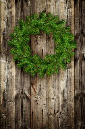Christmas wreath from pine twigs on wooden background