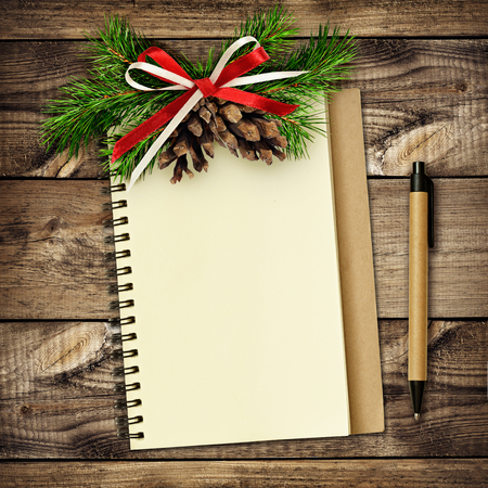 Notebook and pen with Christmas decorations on wooden background