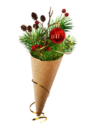 cornet: Christmas bouquet with pine twigs, cones, berries and red ball in a craft paper cornet isolated on white