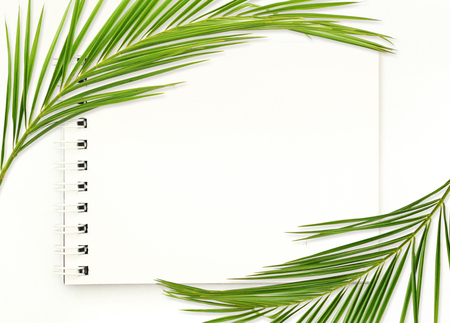 Notepad with white empty page and palm leaves on white background. Flat lay. Top view.