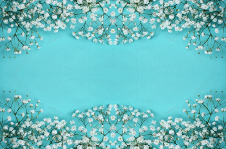 White gypsophila flowers borders on blue textile background
