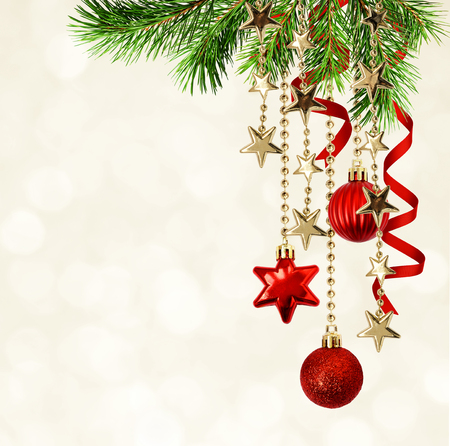 Christmas background with green pine twigs, hanging red decorations and silk twisted ribbons. Festive bokeh. Stock Photo