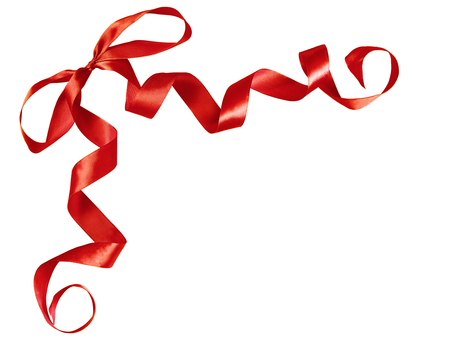 Curled red silk ribbon bow isolated on white background. Corner arrangement. Stock Photo