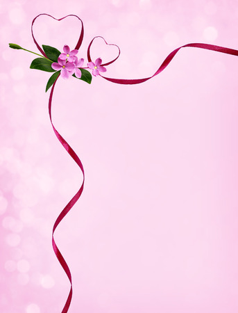 Pink silk ribbon hearts and small flowers in corner arrangement for Valentines day on pink holiday background Stock Photo