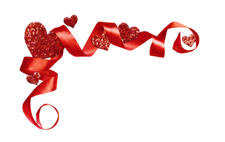 Corner arrangement with red silk twisted ribbon and glitter hearts isolated on white background. Decoration for Valentine's Day. Stock Photo