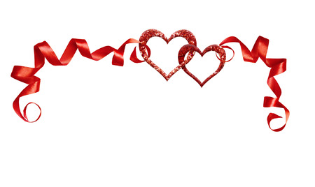 Frame with red silk twisted ribbons and two glitter hearts isolated on white background. Decoration for Valentine's Day.