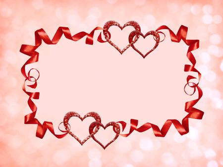 Frame with red silk twisted ribbons and glitter hearts on holiday bokeh background for Valentines Day.